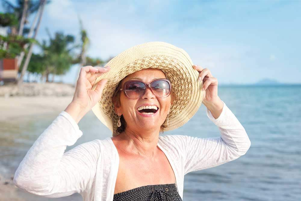 A woman walking on the beach, smiling, and holding her hat